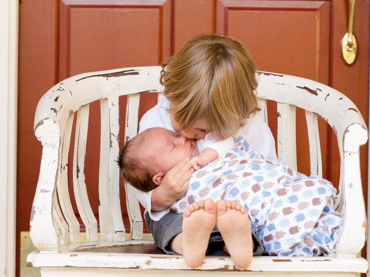 old brother kissing his baby brother